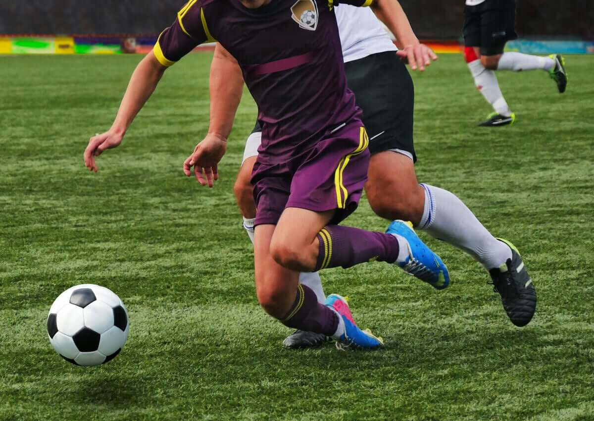 A soccer player suffering an ankle injury during a game.