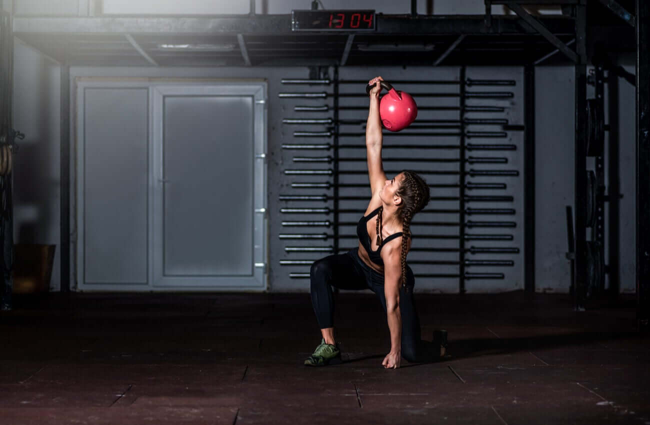 A woman doing a kettlebell grinder.