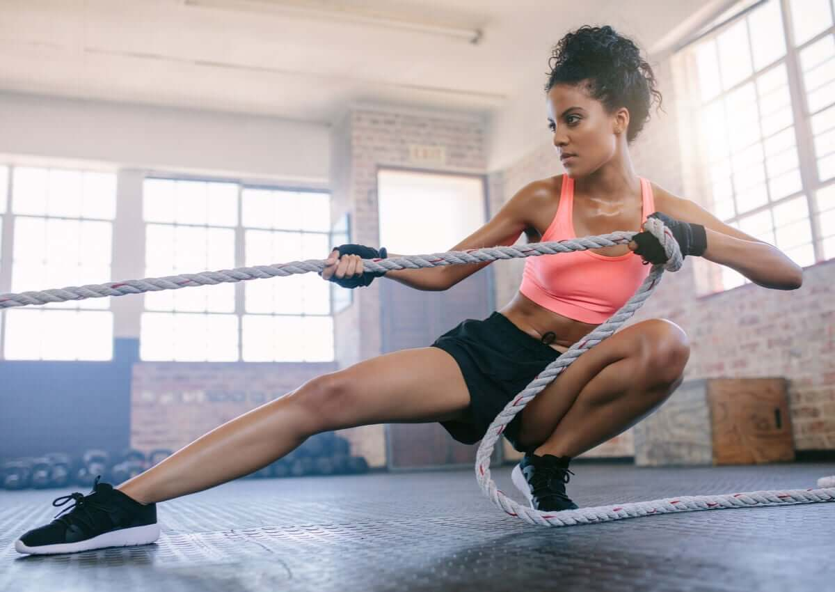 A woman tugging on a rope in a gym.