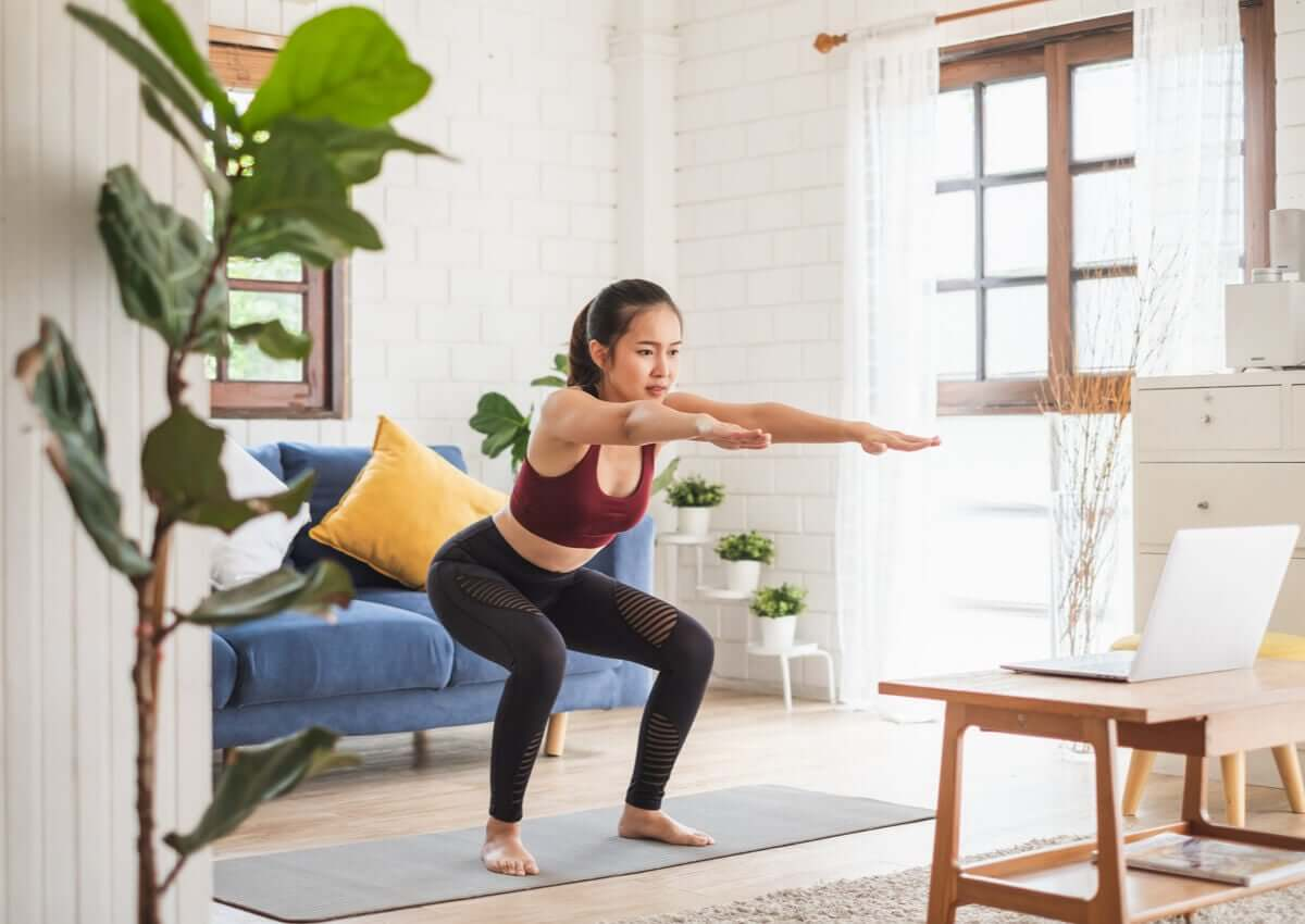A woman doing an online cardio yoga class at home .