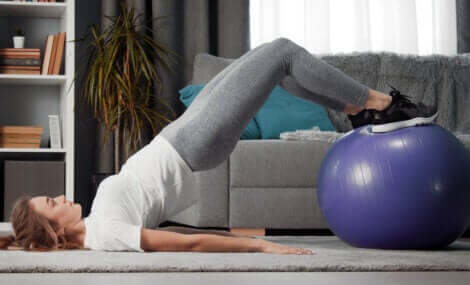 A woman doing a glute bridge with a fit ball.