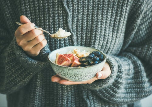 healthy breakfast; person in knitted jumper with bowl of fruit