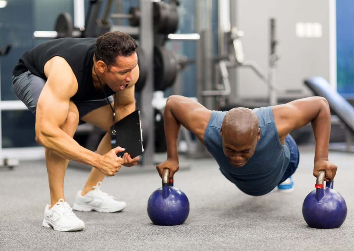 A man doing push-ups with his personal trainer.