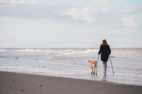 A woman walking with poles along a beach.