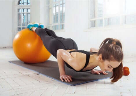 A girl doing push-ups using an exercise ball.
