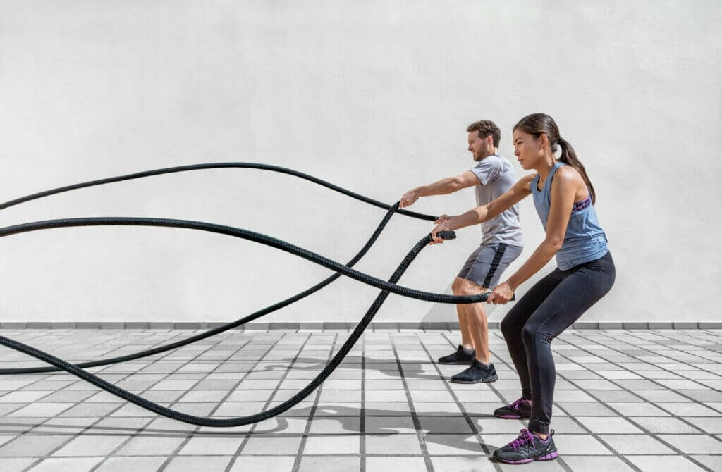 two people using ropes in the gym