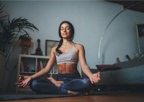 woman practicing yoga, sitting on living room floor in gym wear