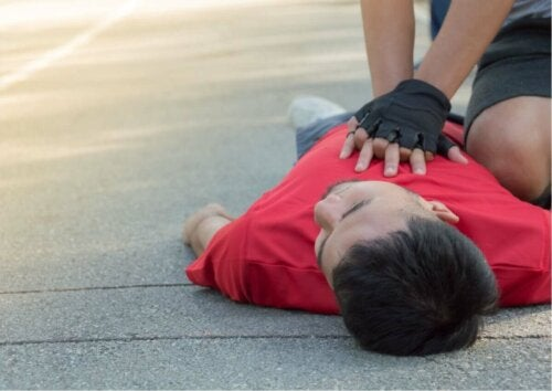 another man lying on the floor with someone administrating CPR with gloves on
