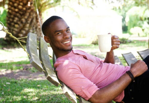 man chilling in the garden with a cup of coffee smiling and resting