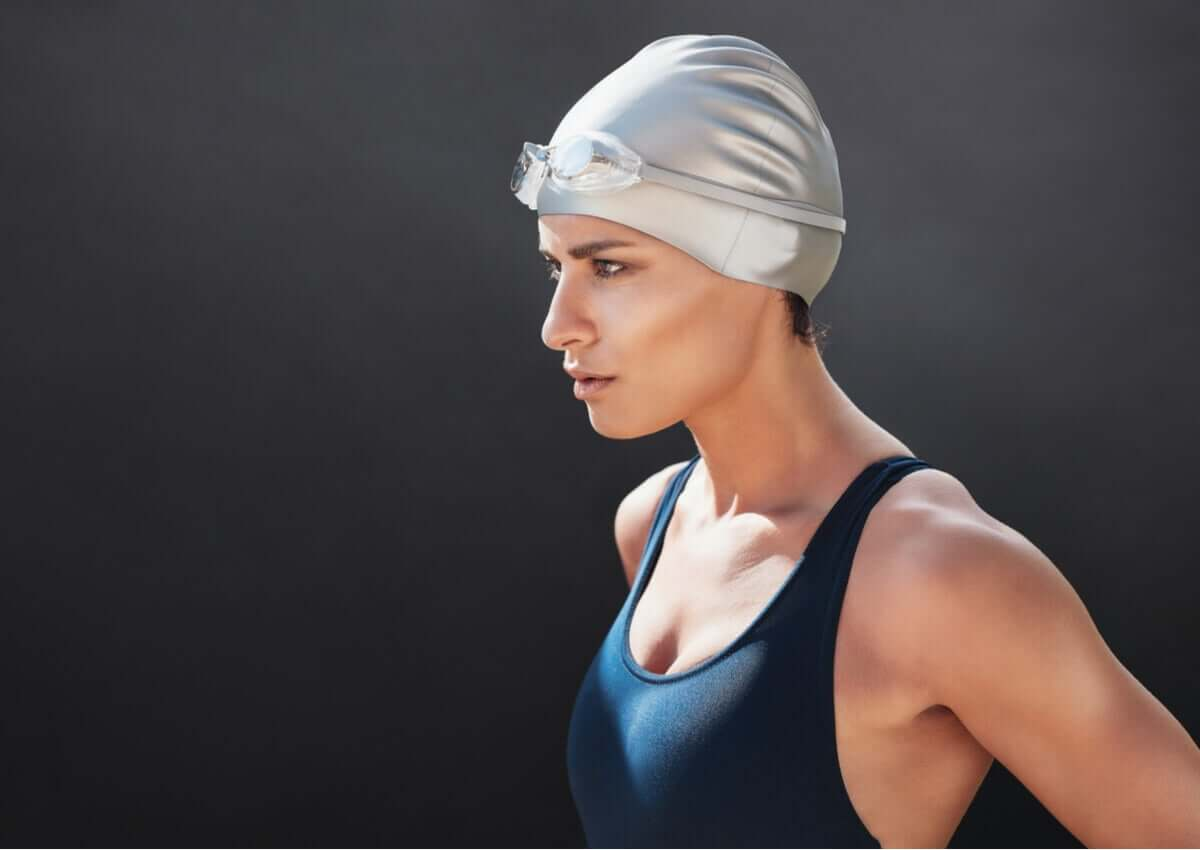 woman contemplating her game plan about to swim wearing swimming cap and bathing suit