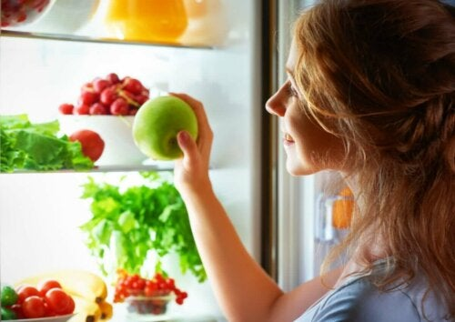 woman opening fridge to get a little snack an apple with loads of other fruit and veg in the fridge